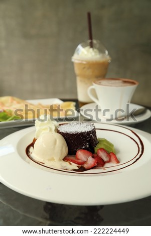 Chocolate Lava Cake with ice cream and beverage in cafe