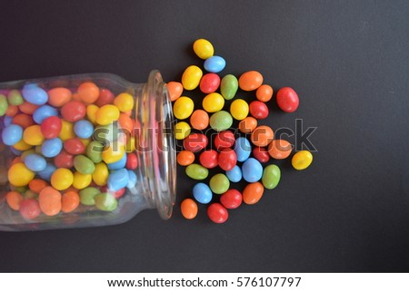 chocolate lentils in a jar on a black ground with colored background #576107797