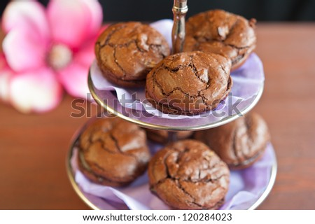 chocolate macaroons on the shelf for candy, purple cloth, pink flower in the background, dark wooden table