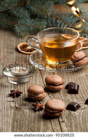 Chocolate macaroons with pieces of black chocolate< lightning candle and cup of hot tea on old wooden table
