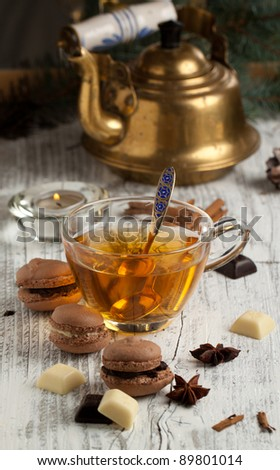 Chocolate macaroons with pieces of white and black chocolate and cup of hot tea on old wooden table