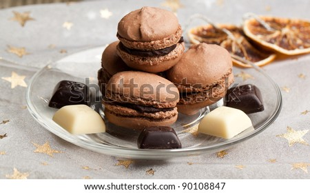 Chocolate macaroons with pieces of white and black chocolate on christmas cloth with golden stars