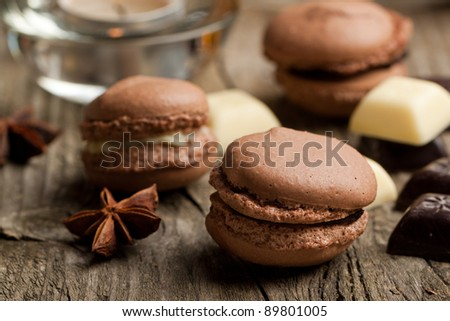 Chocolate macaroons with pieces of white and black chocolate on old wooden table