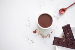 Chocolate milk in white cup with bar chocolate in whit plate on white background. coco hot drink in the morning for health. World Chocolate Day and snack or breakfast concept. flat lay copy space.