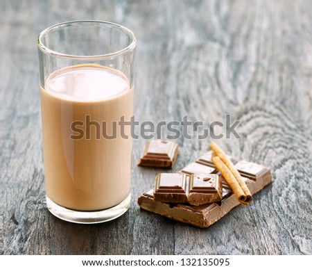 Chocolate milk with chocolate and cinnamon on dark wooden table.