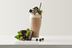 Chocolate milkshake with cream decorated chocolate portions and balls around on white wooden table and light isolated background. Front view.