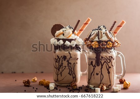 Chocolate  milkshake with ice cream and with whipped cream, marshmallow, sweet popcorn, cookies, waffles, served in glass mason jar. 'Freak or crazy' sweet shake. Stock photo ©