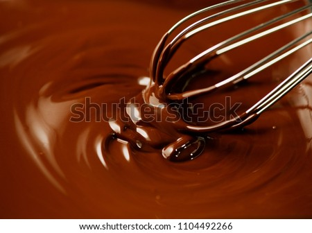 Chocolate. Mixing melted liquid premium dark chocolate with a whisk. Close up of liquid hot swirl. Confectionery. confectioner prepares dessert icing