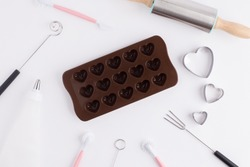 Chocolate mold and Bakery tools on white background. Mold heart shape for concept valentines day.