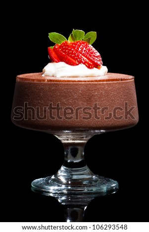 Chocolate mousse dessert with strawberries and cream. Isolated on black.