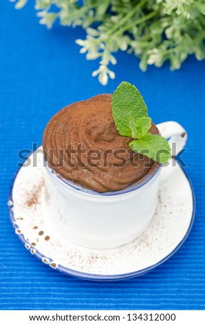 chocolate mousse in a cup garnished with mint on a blue background, top view