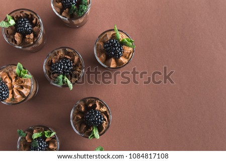 Chocolate mousse in glasses, top view. Desserts as part of party dessert stand. Candy bar and catering concept for birthday, wedding and other holiday celebration, copy space