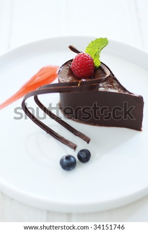 chocolate mousse, styling with cherry, chocolate roll and mint leave.