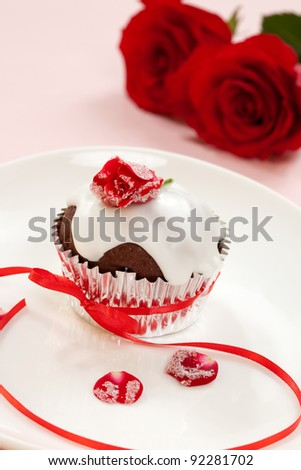Chocolate muffin garnished with sugar frosted rose and vanilla icing. Valentine's day or wedding desert.