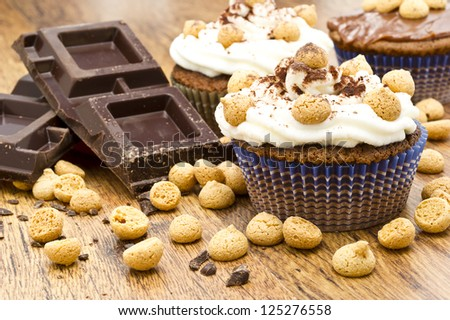chocolate muffin with italian pastries called amaretti on wooden table