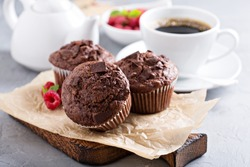 Chocolate muffins with a cup of coffee and fresh berries on the table