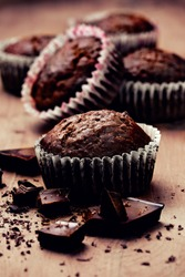 chocolate muffins with chocolate slices on wooden background (Toning, dark)