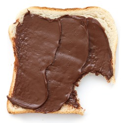 Chocolate nut spread on sliced white bread shot from above.