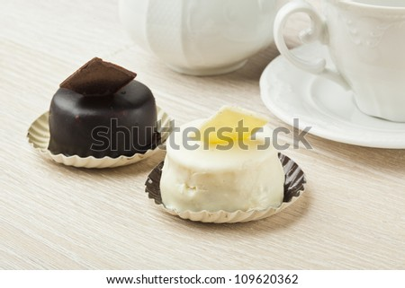 chocolate pastry little cake with tea cup on  wooden table