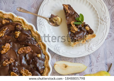 Chocolate pear tart. A portioned slice of chocolate pear tart on a white plate