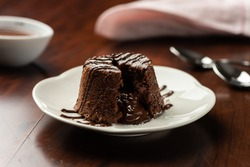 chocolate petit gateau and cocoa with hot melted inside . background and recipe ingredients on wooden table