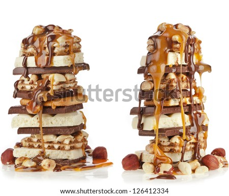 Chocolate pieces and caramel syrup poured on stack isolated on white background