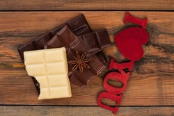 Chocolate pieces on vintage wooden background.