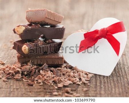 Chocolate pieces  on wooden background with heart symbol