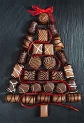 Chocolate pralines Christmas tree on stone black table