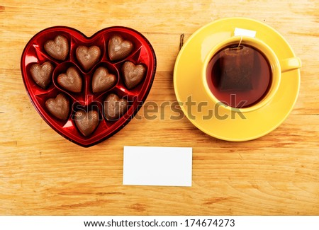 chocolate pralines in red heart shape box on table