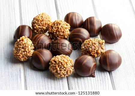 chocolate pralines on white wooden table