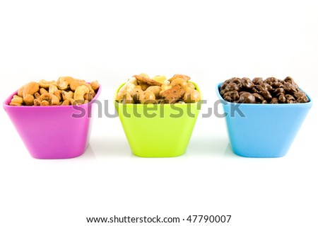 Chocolate raisins, cashew nuts and mixed nuts in colored bowls isolated on white background