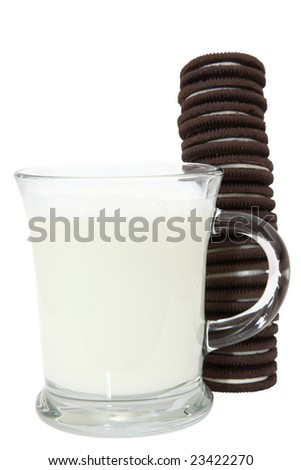 Chocolate sandwich cookies filled with creamy vanilla icing stacked next to a glass of milk.