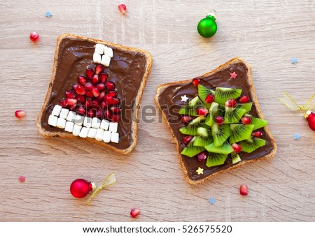Chocolate sandwich with pomegranate and marshmallow Santa hat and kiwi Christmas tree - creative idea for kids breakfast, dessert or holiday meal, Christmas food art