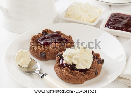 Chocolate scones with chocolate chips, topped with raspberry jam and whipped cream.