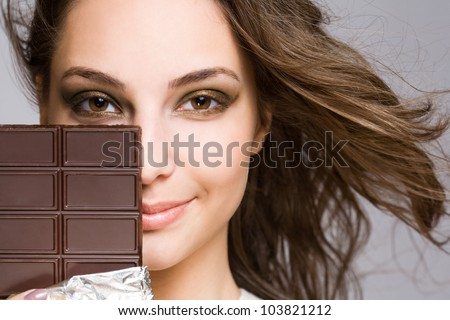 Chocolate seduction, portrait of a brunette beauty with tasty dark chocolate.
