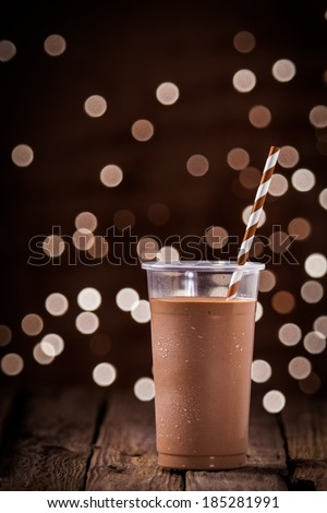Chocolate smoothie or milkshake with a sparkling bokeh of party lights in the background standing on a rustic wooden table at a restaurant or bar
