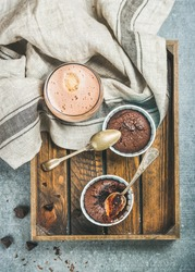 Chocolate souffle in individual baking cups and chocolate mocha coffee in wooden serving tray over grey concrete background, top view