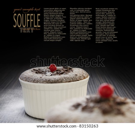 Chocolate souffle with chocolate chips and red currant and copyspace isolated on black background.