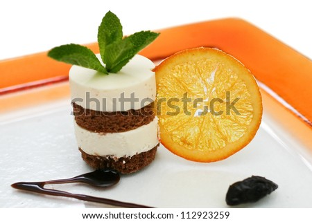 Chocolate sponge layered cheesecake with a dried orange wheel