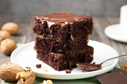 Chocolate spongy brownie cakes with walnuts and melted chocolate topping on a stack