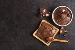 Chocolate spread on slice of bread with spoon, melted cream white bowl and pieces of chocolate with nuts on a stone table. Popular desser food. Top view.