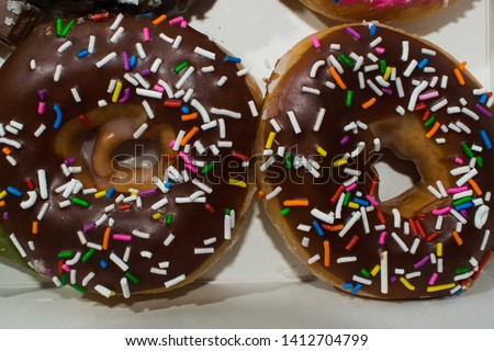 Chocolate sprinkled doughnuts on a white background
