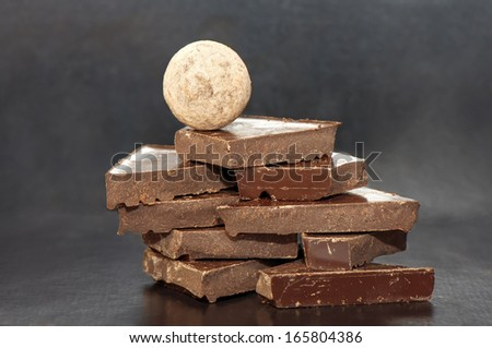 Chocolate stacked slices with a chocolate ball on the top on black background