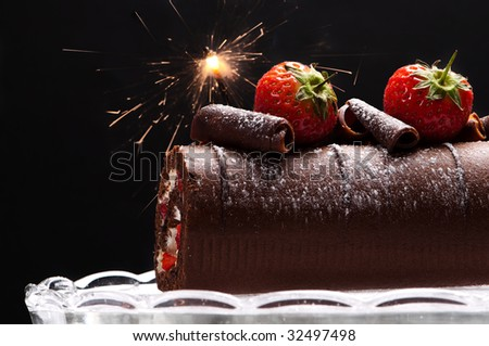 Chocolate swiss roll with strawberries and sparkler decoration