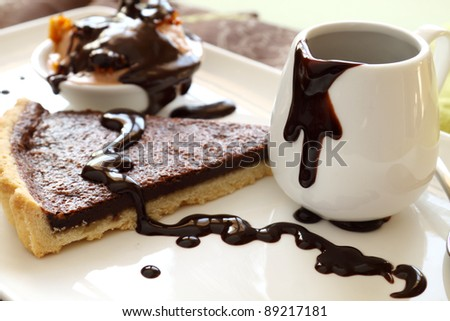 Chocolate tart slice and ice cream with melted chocolate from a jug.