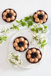 Chocolate tart with salted caramel filling and fresh blackberries. Cherry flowers on background. Copy space.
