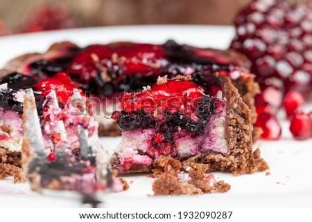 chocolate tartlet with fruit and berry filling, round tartlet with strawberries and blueberries in butter cream, baked tartlet dessert, closeup