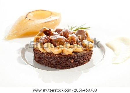 Chocolate tartlet with nuts toffee on white plate. Delicious dessert - Caramel nut tart with pear. Traditional pastry - Butterscotch tartlet with hazelnut, almond and pecan. Autumn dessert