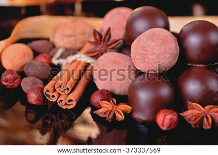 Chocolate truffles and chocolates with spices on a black background